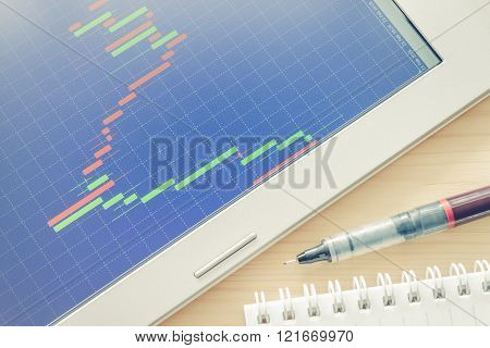 Stock Or Forex Graph Or Candlestick Chart On Blue Screen And Pen And Notebook Vintage