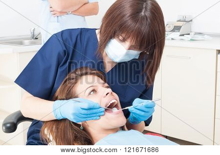Oral hygienist or orthodontist at work on a female patient with beautiful teeth