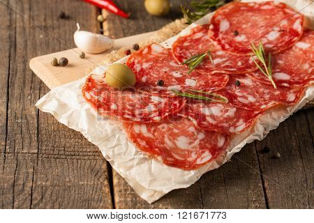 Chorizo sausage and salami, thin cut. spanish salami on the wood background with spices, paprika, pe