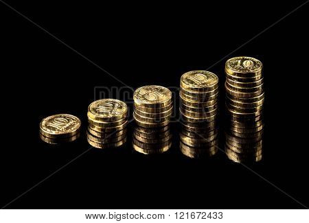 hand deliver a stack of coins graph profit growth on black background