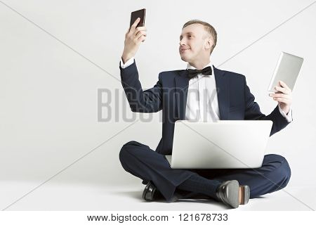 Communication Concept. Handsome Caucasian Man In Suit Using Digital Pad, Smartphone And Laptop For M
