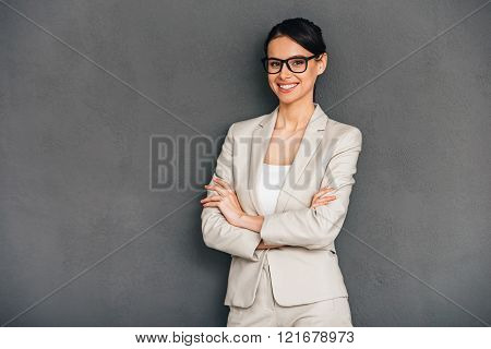 Cheerful and confidant. Cheerful young businesswoman in glasses keeping arms crossed and looking at camera with smile while standing against grey background