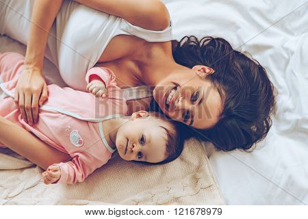 Morning hugs. Top view of cheerful beautiful young woman looking at camera with smile while lying in bed with her baby girl