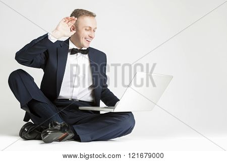 Happy Smiling Caucasian Man In Blue Suit With Laptop Chatting And Showing High Five. Sitting On Floo