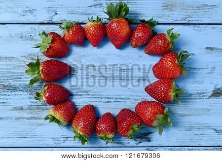 high-angle shot of a pile of appetizing strawberries forming a circle on a blue rustic wooden surface