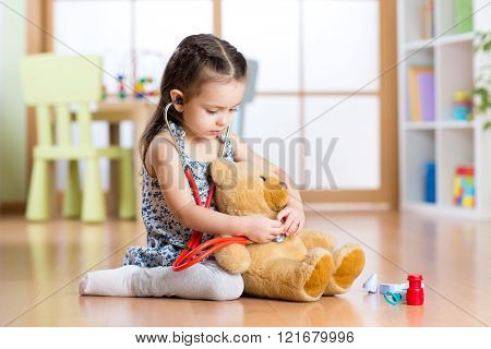 Little child girl with stethoscope and teddy bear sitting on floor, on home interior background