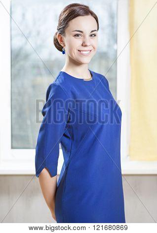 Elegant and Smiling Caucasian Brunette Female in Blue Official Dress.Indoors Shot