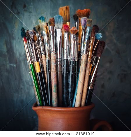 Paintbrushes In A Jug From Potters Clay On Dark Panting Background.