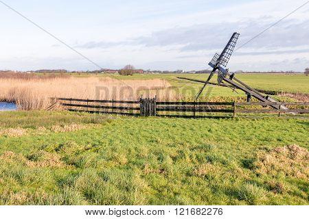 Meadow with Paaltjasker windmill in nature area Sanpoel in Friesland Netherlands.