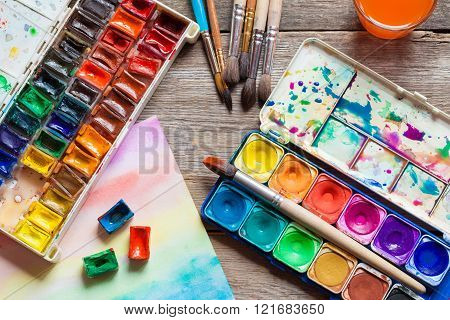 Set Of Watercolor Paints, Brushes For Painting And Paper Sheet Of Painting On Old Wooden Background.