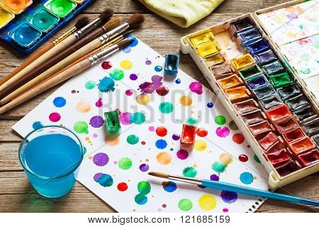 Watercolor Paints, Brushes For Painting And Paper Sheet Of Painting On Old Wooden Background. Top Vi