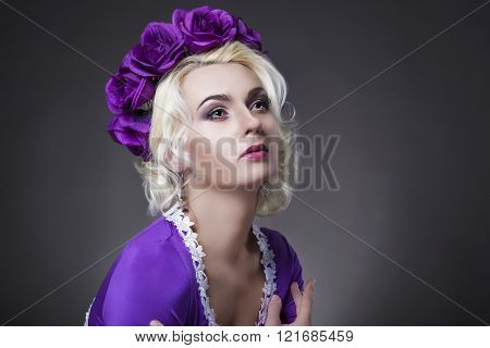 Beauty Concept And Ideas. Caucasian Female Posing In Purple Dress With Flowery Violet Crown.
