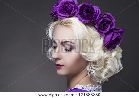 Closeup Portrait Of Blond Woman Wearing Unique Flowery Purple Crown. Posing Against Black
