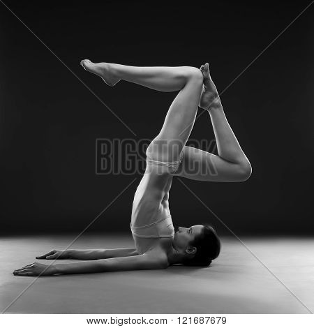 Naked yoga. Beautiful sexy body of young woman on gray background. Low key black and white studio photography