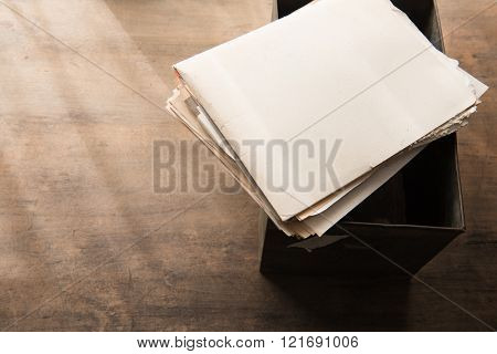 Old documents from an storage box or archives, with by-the-window type light coming in. Shallow depth of focus.