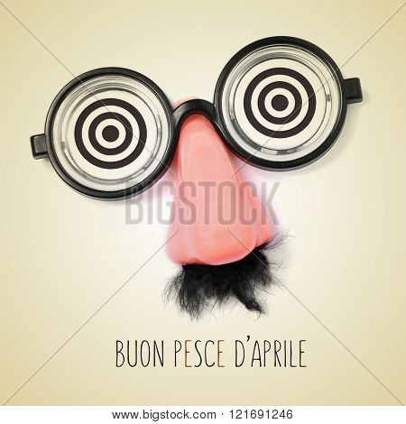 fake eyeglasses, nose and mustache and the sentence buon pesce d aprile, happy april fools day written in italian in a beige background, with a retro effect