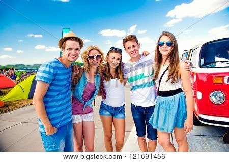 Teenagers at summer music festival by vintage red campervan
