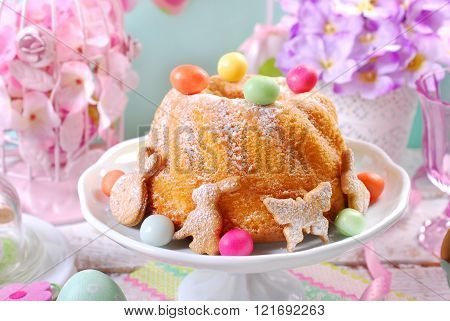 Easter Ring Cake With Candy Eggs And Cookies On Spring Table