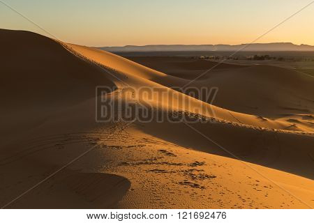 shadows on the sand dunes of Merzouga, Morocco at sunset