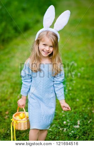 Smiling Little Girl With Long Blond Hair Wearing White Rabbit Bunny Ears And Blue Knitted Dress