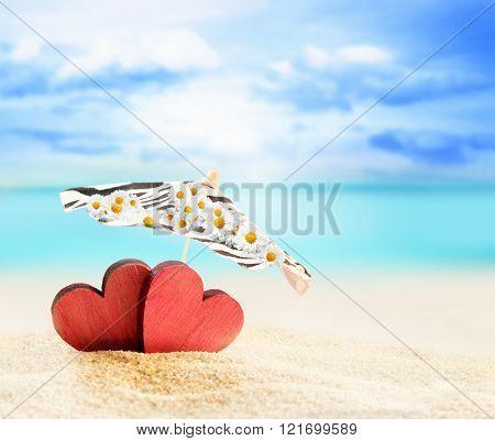 two hearts under umbrella on a sandy beach