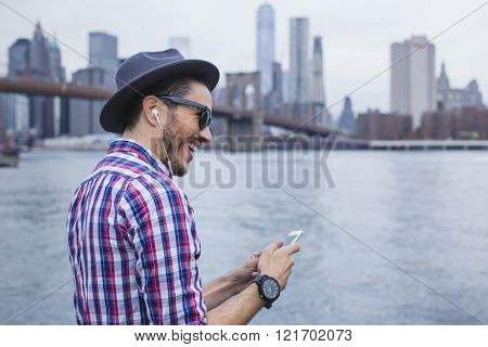 Hipster listening music with his smartphone in Brooklyn, New York