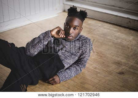 Portrait of a young afroamerican indoors wearing a jumpsuit lying in the floor