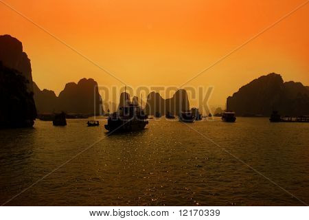 Limestone outcrops in Ha Long Bay and tourist boats at sunset