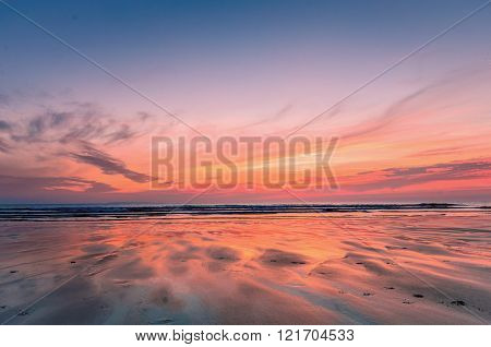 The goden glow of dusk at woolacombe beach in Devon