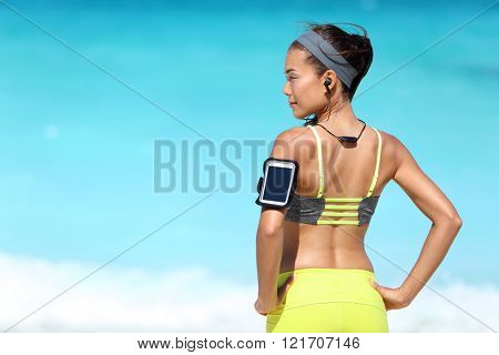 Fitness runner woman with fit back wearing phone armband and wireless headphones on ocean background. Multiracial exercise girl jogging on summer beach with sports smartphone touchscreen for app.