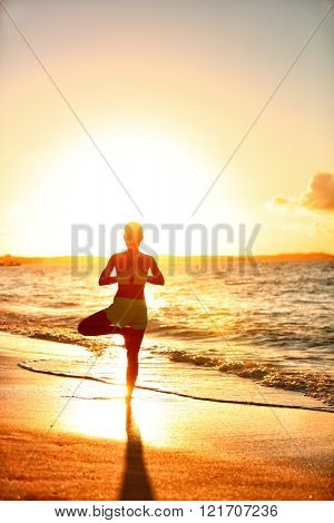 Meditation woman practicing Vriksasana tree yoga pose on beach at sunset. Serene young adult silhouette in morning sun flare balancing meditation doing a body workout. Wellness concept.