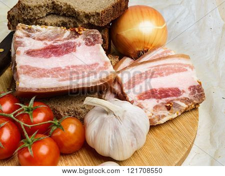 Two Pieces Of Salty Bacon With Rye Bread