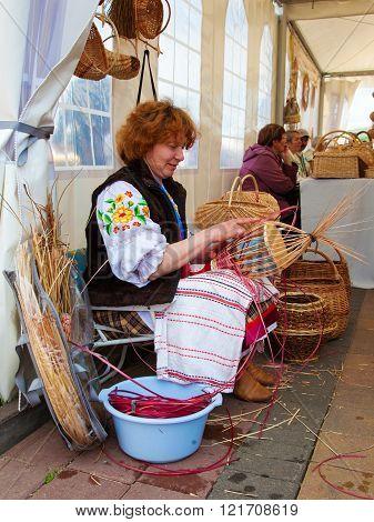 Minsk, Belarus, 09-may-2014: Woman Weaving A Traditional Wicker Basket By Handmade At Market. Minsk,