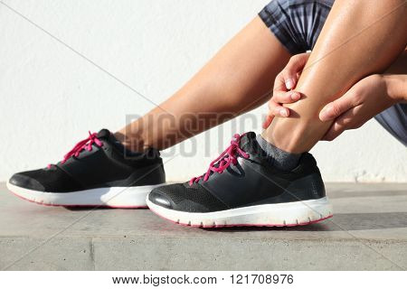Ankle jogging injury female runner holding painful sprained ankle. Legs and running shoes closeup of woman hands gripping on leg in pain because of sore and injured joint and muscles in ankles.