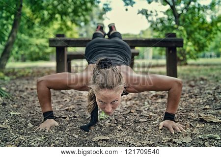 Female athlete exercising doing push ups on fitness trail