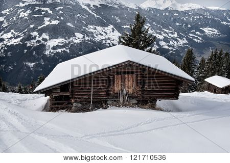A wooden shed on the snowy slopes of the Karspitz Mountain viewed from above, Zillertal, Austria