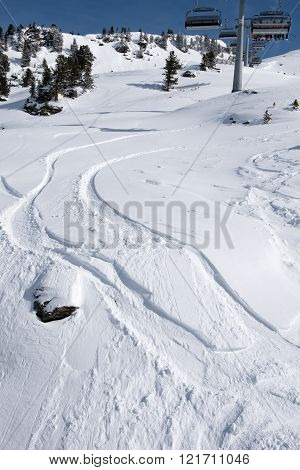Snow tracks bending in a curve under the ski lift in the Zillertal Arena, Austria