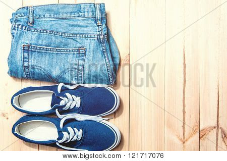 Youth Blue Sneakers  And  Jeans  On Wooden Background With Copy Spase