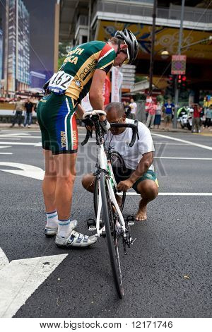 KL, MALAYSIA - 15 February: South African cyclist gets a punctured wheel replaced, at the le Tour de Langkawi race, Stage 7, KL Criterium. in Kuala Lumpur Malaysia 15 February 2009