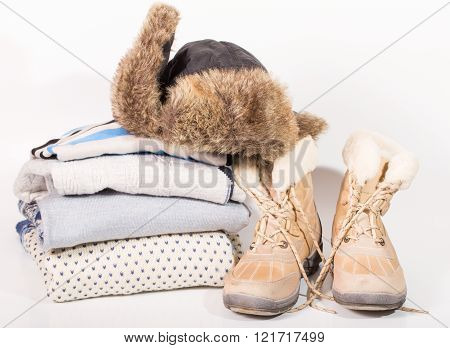 Warm clothes for cold weather. Boots a pile of sweaters a cap with fur on a light background.