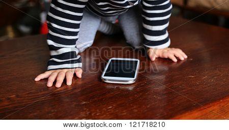 Smart Phone With Cartoons Between Baby Hands