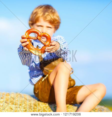 Two little kid boys and friends sitting on hay stack