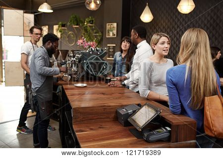Mixed racial group of people in a modern cafe, baristas working behind the wooden counter and customers chatting while waiting for their coffees to be made