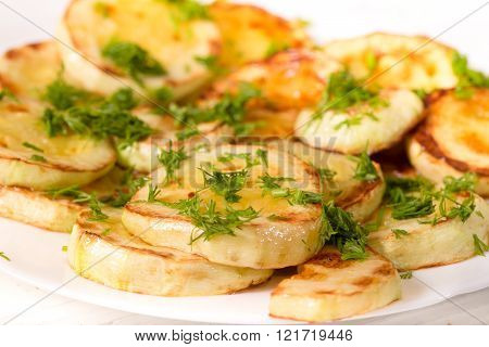 Appetizing zucchini fried in oil and strewed with greengrocery. Close up small depth of sharpness