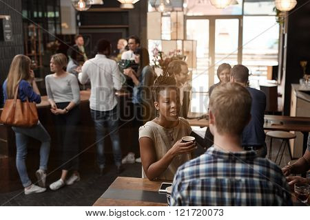 African woman sitting with friend at a high table in a busy coffee shop with modern decor and many other customers in the background