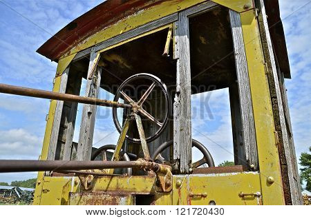 A very old road grader has a wooden cab and long steering mechanisms