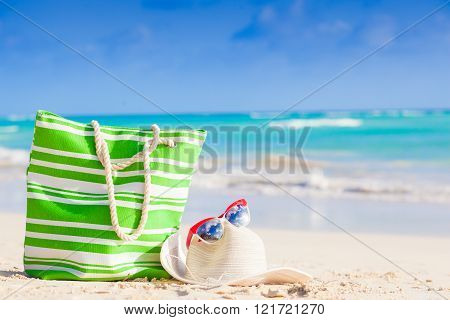 beach bag, sunglasses and straw hat on tropical beach