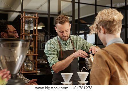 Trendy hipster barista carefully pouring fresh coffee through a ceramic filter in a modern coffee shop while a customer watches her order being made