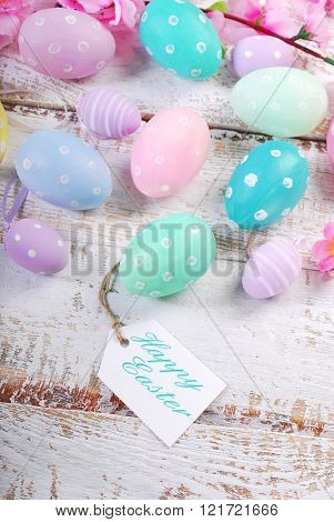 Easter Background  With Pastel Color Eggs And Greetings On Paper Tag
