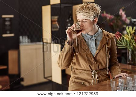 Modern cafe with a young blonde woman in trendy winter clothing taking a sip of fresh coffee with soft morning light falling on her